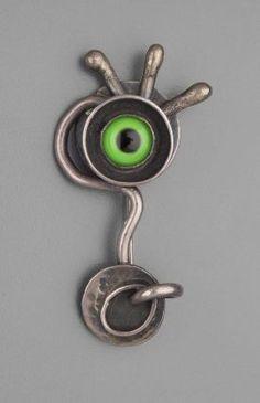 Brooch |  Sam Kramer, c. 1950.  Silver, green glass taxidermy eye.