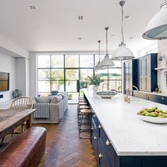 The navy blue kitchen zone encompasses the contemporary country design, including a stunning six-metre-long marble-topped island and breakfast bar with plenty of space to receive guests. The white quartz worktop looks super fresh against the navy blue uni Navy Kitchen, Living Room Kitchen, Long Kitchen, Kitchen Units, Kitchen Modern, Kitchen Cabinets, Modern Farmhouse, Sofa In Kitchen, Open Plan Kitchen Dining Living