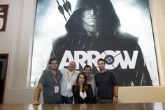 Posing in front of the series' sexy key art at the Warner Bros. booth at Comic-Con 2012, it's ARROW's cast and producers; from left: Andrew Kreisberg, Marc Guggenheim, Katie Cassidy, David Nutter and Stephen Amell (© WBEI. All Rights Reserved.)