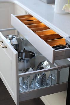 Fabulous kitchen boasts a lit cutlery drawer stacked over a pot and pan drawer accented with a pot and pan lid rack.
