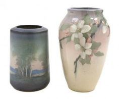 A Rookwood Pottery Vase, Edward T. Hurtley,1919, of circular tapering form, decorated with a landscape scene, executed in an iris glaze, impressed 2103 V, together with a 1906 ovoid example by Lenore Asbury decorated with cherry blossoms