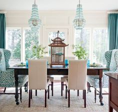 Love that the end chairs are different to the middle, and that they completely encase the person who sits on them, also loving the patterns. The colours are divine, and the bird cage in the middle is very cute. ~Sarah    studding dining room anchored with wing chairs.
