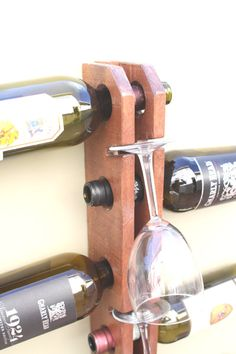 A Unique styled wall mounted wine rack stores wine vertically and artfully. The creative functionality of this piece make it a show piece that would grace any kitchen or dining area.  - Made of Western Cedar - Completed with a clear satin finish - Your choice of stains: Mahogany (pictured), golden oak or Burned barn (espresso) - Holds 9 FULL Bottles and 4 Wine Glasses. - Dimensions: 2.5 W x 3.5 D x 36 H. With bottles wine rack is 21.5 W - Designed to hold 4 wine or stemware glasses with a…