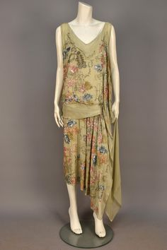 WORTH BEADED and SEQUINED SILK DRESS, 1925. /  Sleeveless pale celadon chiffon decorated with a stylized floral in pastel sequins, crystal beads and rhinestones, having V-neck and back, hip sash and long side streamers, silk underdress.