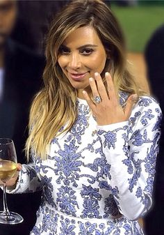 "It's official! Kim Kardashian and Kanye West are tying the knot. The rapper proposed to the reality show diva with a flawless, D color 15-carat cushion cut diamond ring by Lorraine Schwartz. Schwartz said Kanye was very much a part of the design process, ""He wanted the diamond to look like it was floating on air. Everything was his idea from beginning to end."""