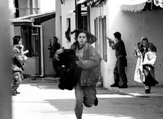 """A girl runs across the sniper alley in south Bosnian town of Mostar, while the territorial defence fighters try to cover a few civilians trapped between houses by the sniper fire, April 1992"".    by Zoran Bozicevic ( http://www.zoranbozicevic.com/ )"