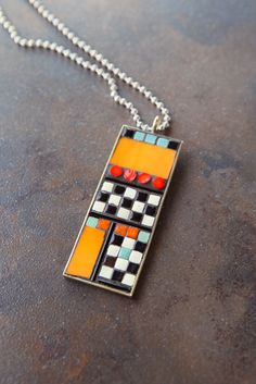 Tangerine art glass and black and white checkerboard mosaic pendent necklace. $65.00, via Etsy.