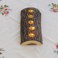 Our Wedding Centrepieces This candle holder is made from a split found log and holds 5 tealights. It is wide and not tall, almost appearing to be set into the table. This candle holder is 13.5 inches long, 5 inches wide and 1.75 inches tall