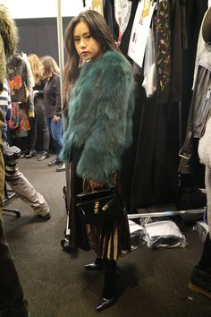 Les fourrures, moonboots, bonnets et autres accessoires de Noël sont de sortie. C'est un carnaval de superpositions, repéré en backstage du défilé Desigual. Plutôt que faire grise mine, on ajoute de la couleur (parfois trop): un état d'esprit dont il n'est pas superflu de s'inspirer. Dans de telles conditions. Focus: fashion week à New-York, backstage, fourrure bleue, jupe longue dorée et plissée, escarpins noirs