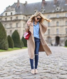 Caroline Louis is wearing a camel coat and shoes from Zara, ripped jeans from Frame Denim, Chambray shirt from TopShop and the red bag is from Chanel