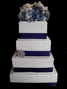 Navy blue and white wedding cake. I like the crystals and brooch.