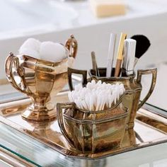A vintage tea set is now used to store and hold makeup brushes and cotton pads creating an elegant addition to a bathroom or bedroom vanity.