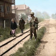 French civilians pass a British military policeman of No. 6 Beach Group in La Brèche d'Hermanville, 6 June 1944
