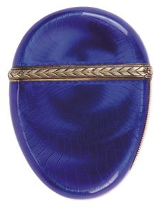 A FABERGE SILVER AND GOLD TRANSLUCENT ENAMEL MATCH SAFE, HENRIK WIGSTROM, ST. PETERSBURG, CIRCA 1900. The compressed egg form safe with translucent royal blue enamel over an engine turned wavy ground. The hinged lid with two colored gold leaf banding and the side with reeded striking surface.