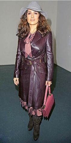 """SALMA HAYEK Pharell already won the Hat Person of the Year Award, but that doesn't stop Salma from throwing her, you know, hat in next year's ring. She pairs the wide-brim gray design with a pleated plaid dress and a leather trench at the """"Tryptiques Atypiques"""" photo exhibition in Paris."""