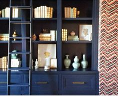 Caitlin Wilson design. Jennifer Latimer 24K gold coral paintings, styling bookcase, built ins, white navy gold.