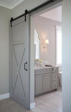Gray walls highlight a gray barn door on black rails leading to an en suit bathroom featuring a gray washstand accented with polished nickel hardware and topped with a white marble countertop fitted with an oval sink and a polished nickel antique hook and spoiut faucet positioned under a white arched mirror lit by a Bryant sconce illuminating wood like tiled floors and light gray bathroom walls.