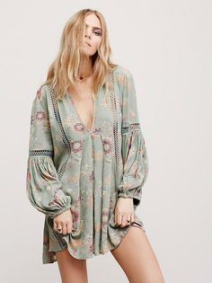 Just the Two of Us Printed Tunic   Crinkly babydoll printed style swing tunic featuring crochet insets and pleat detailing. V-neckline and elastic cuffs with wide statement sleeves.