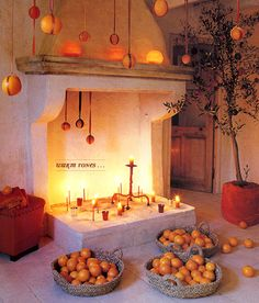 hanging oranges, spanish fireplace filled with candles, orange tree, woven baskets of oranges
