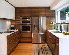 This transitional kitchen design features modern walnut cabinets against white wall accents & white countertops.