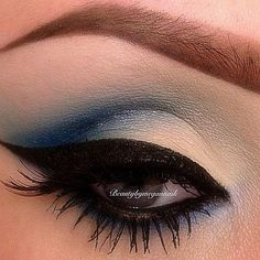 A hint of blue shadow with pale over the lid. Liquid eyeliner along the lash line and swept out at the edge.