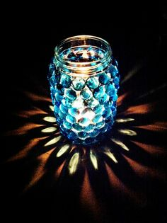 Tea light decoration. Used a mason jar (can also use old wine bottle or wide vase) hot glued gems ($2 at Craft store) and place a tea light candle inside. Beautiful, easy to make and cost me only $8 !!!
