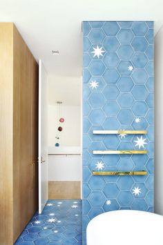 The sky blue tile turns to cover an accent wall too, and beautifully complements the gold towel bars.