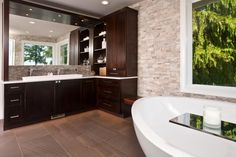 This bath is a blend of contemporary sleek elements like the chrome fixtures and glossy tile, that contrast with the natural elements such as the matte tile floor and the stacked stone walls. Its a neutral palette that anyone could relax in.