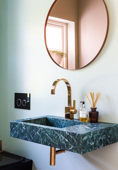 Elegant bathroom details - a stunning green marble sink with luminaire and mirror in brass.
