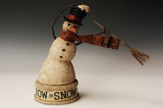 SNOW SNOW SNOW by PETER BRETZ -  a carved snowman holding onto his hat on a blustery day