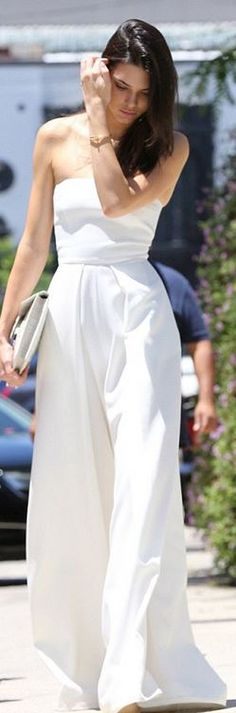 Who made  Kendall Jenner's white strapless jumpsuit, gold jewelry, key chain, and gray clutch handbag?
