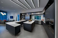 This streamlined, open plan kitchen, designed by Angelica Henry, shows the dramatic side to modern design. The black laminate cabinetry and the stainless steel appliances and accents marry well with the linear elements in the room, such as the lighting arrangement and long, angular countertops, to give the space a lean, industrial and high-tech look.
