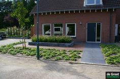 Hoogte verschillen met stapelblokken, duidelijke entree naar de voordeur en onderhoudsvriendelijke beplanting.