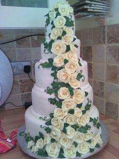 5 tier white wedding cake with creme roses and deep green ivy