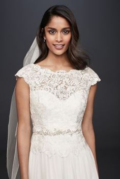 This soft A-line lace and chiffon wedding dress will make a beautiful first impression. The illusion lace bodice is softly scalloped at the waist and along the V-back, and the slim satin waistband is