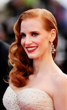 #JessicaChastain rocks the #Cannes red carpet looking like a 50s pin-up with her hair curled to one side and a slick of red lipstick.