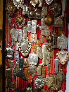 "Milagros means ""miracles"". These traditional metal charms are used to help that saint perform a miracle (hence the word ""milagro""). There is supposedly a milagro for virtually every animal, every organ and every imaginable malady. I was smitten by the metalwork and repousse. This was a stealth shot. I got quite sneaky with my little spy camera."