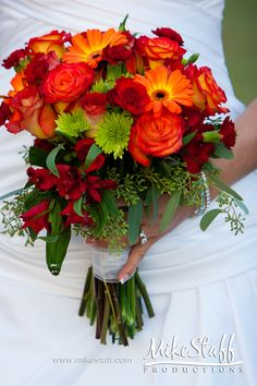 Mini dark red carnations, red ranunculus, a few red dark roses, tan/champagne/cream roses or carnations or lilies.