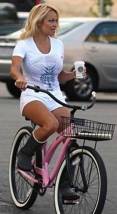 Pamela Anderson rides a pink cruiser bicycle on her way over to Hot Pepper Dave's to help in the garden.