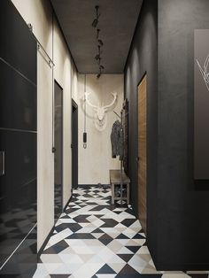 Industrial style entry / entrance wtih dark charcoal walls, bold geometric flooring