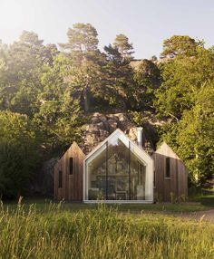 The family retreat abuts a rocky cliff in Herfell, Norway. The central cabin provides communal living spaces, while the two cabins that flank it are used as private sleeping quarters.