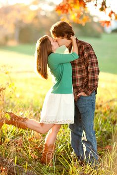 engaged couple sharing a kiss, foot-popping kiss, vintage farm engagement session