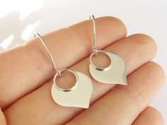 Simple lotus petal earrings dangle from semi large open artisan style hoops. These are solid .925 sterling silver and carry a very high shine!
