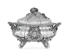 A WILLIAM IV SILVER SOUP TUREEN MARK OF ROBERT GARRARD, LONDON, 1837 Fluted oval, on four scroll, rocaille and acanthus feet, the gadrooned rim with two leaf-clad and dog's-mask bracket handles, the fluted domed cover applied with a cauliflower florette and leaf finial, each side with applied cast coat-of-arms, crest and motto, the cover engraved on each side with a crest