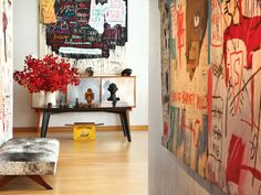 "Three Basquiats take up so much wall space that the entry hall seems ""papered"" in the artist's imagery. At the end of the hall is a table in front of a Perriand console with works by, among others, George Condo and Picasso."