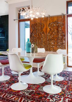 You don't often see mid-century mod Saarinen table & chairs paired with an ornate wooden screen from India or what looks like an antique carpet... but I love this combination. It adds a lot of personality.