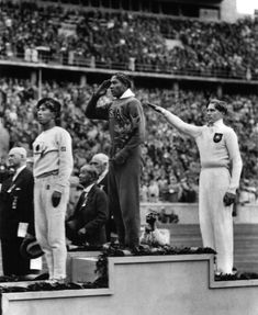 This Aug. 11, 1936 file photo shows America's Jesse Owens, center, salutes during the presentation of his gold medal for the long jump, after defeating Nazi Germany's Lutz Long, right, during the 1936 Summer Olympics in Berlin. Naoto Tajima of Japan, left, placed third. (AP Photo/File)