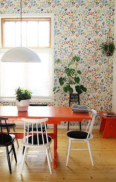 Värikäs ruokahuone on sisustettu kierrätyshuonekaluilla. Värikäs tapetti kokoaa huoneen värisävyt yhteen.