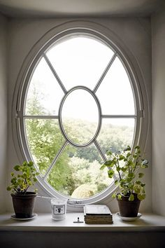 Oval Window in Georgian Country House. Oval window on the stairs with plants, a view of the garden.