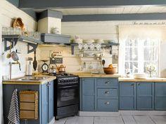SELVLAGET: Det nydelige, blå kjøkkenet er det Arne som har bygget. Den smarte hjørneløsningen med ovnen var hytteeiernes egen idé. Det gamle skiltet har Hilde kjøpt i en interiørforretning i Arendal. Kobberkjelen tilhørte Arnes tippoldeforeldre, og stammer fra tidlig 1800 tallet.